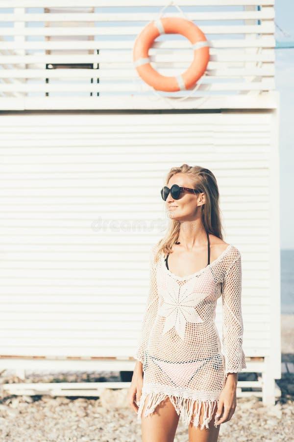 Het modieuze blondemeisje in een zwempak en de zomer kleden zich op het strand tegen de achtergrond van een houten reddingstoren  stock afbeelding