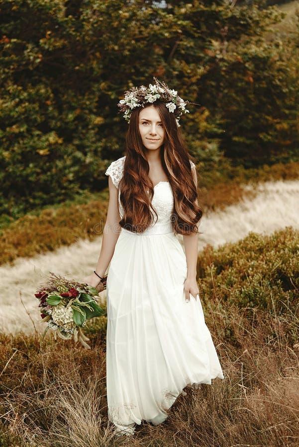 Het modieuze bruid stellen met boeket op achtergrond van bos, luxur stock afbeeldingen