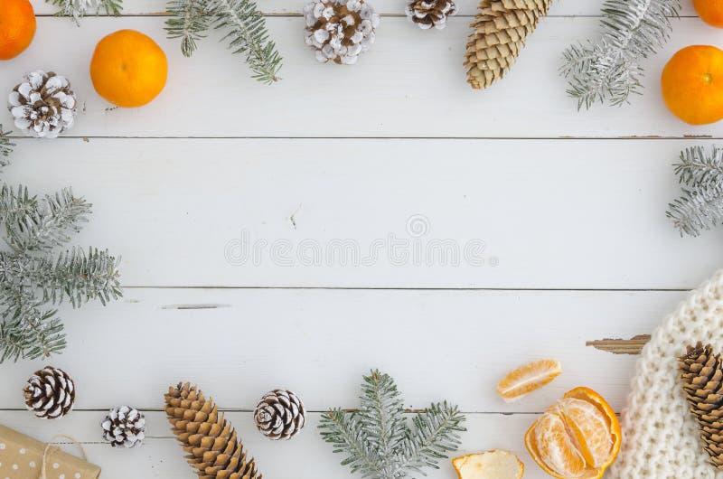 Het modieuze feestelijke Nieuwe jaar, Kerstmis, vrolijk Kerstmiskader van decoratie, sparappel en tak, breide sjaal, gift, sinaas royalty-vrije stock fotografie