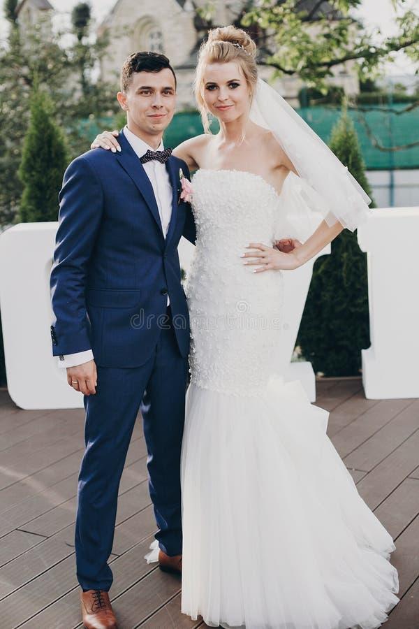 Het modieuze gelukkige bruid en bruidegom stellen bij groot liefdewoord in avondlicht bij huwelijksontvangst in openlucht Schitte stock foto's