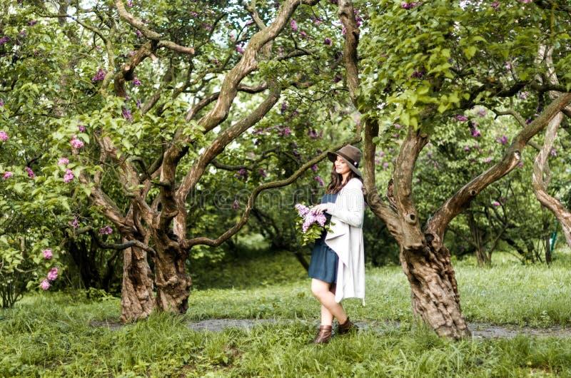 Het modieuze gelukkige meisje bewondert de lilac bloesem in de tuin stock foto's