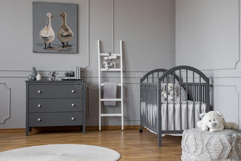 Het modieuze grijze binnenland van de babyruimte met houten meubilair, witte Skandinavische ladder en teddybeer op poef, echte fo royalty-vrije stock afbeelding