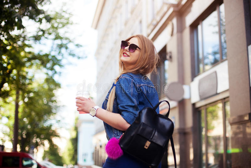 Het modieuze hipstermeisje in de retro jeans past stellend Openluchtlevensstijlportret van gelukkig meisje aan zij loopt onderaan stock afbeeldingen