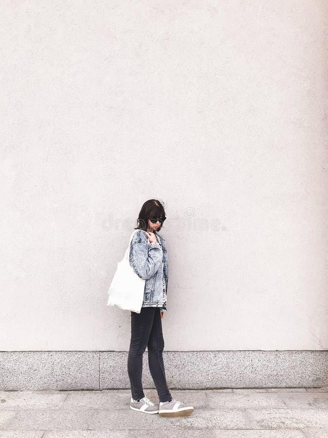 Het modieuze hipstermeisje in denimuitrusting en de totalisator doen het stellen in stadsstraat op in zakken achtergrond van muur royalty-vrije stock foto's
