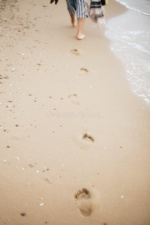 Het modieuze hipstermeisje lopen blootvoets op strand, het houden doet en in hand schoenen in zakken De voetafdrukken op zand slu royalty-vrije stock foto's