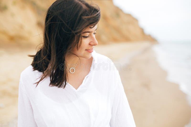 Het modieuze hipstermeisje ontspannen op strand De vakantie van de zomer Portret van gelukkige bohovrouw die van tijd genieten en stock foto's