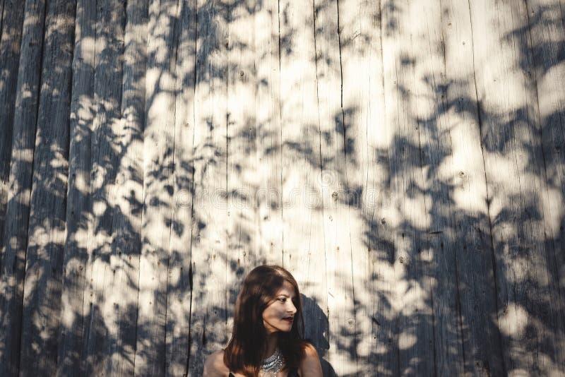 Het modieuze hipstermeisje stellen in zonnige straat op achtergrond van houten muur Bohomeisje in koele uitrusting die zich in zo stock foto