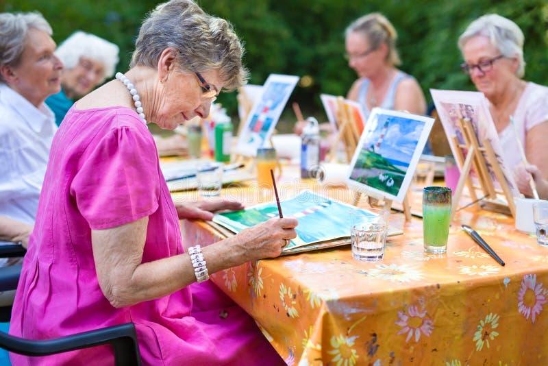 Het modieuze hogere dame schilderen in kunstklasse met vrienden van haar zorghuis voor oud kopiërend het schilderen met waterkleu stock foto's