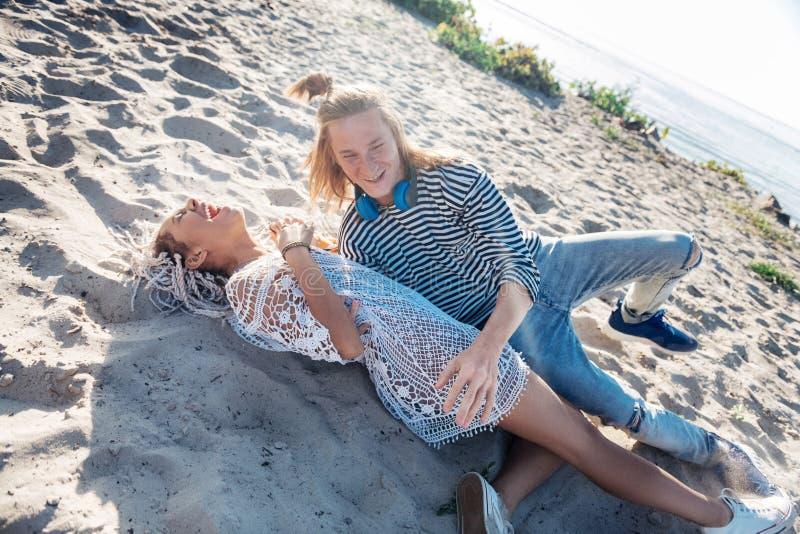 Het modieuze het houden van paar luid lachen uit terwijl het liggen op zandig strand stock foto