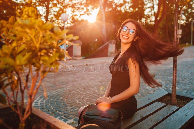 Het modieuze jonge bedrijfsvrouw koelen in de zomerpark Modieuze uitrusting Gelukkig mooi model die bij camera glimlachen royalty-vrije stock foto