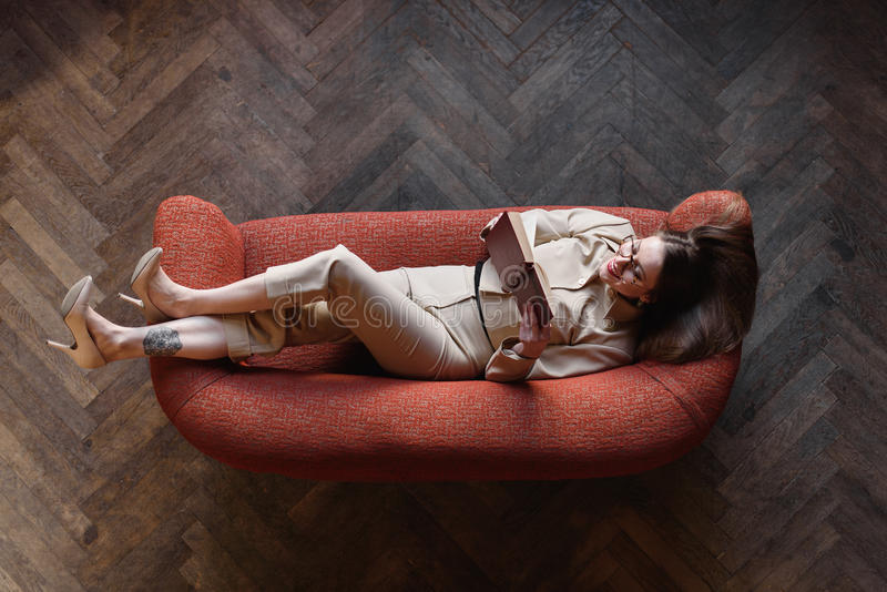 Het modieuze jonge meisje in beige kostuum leest een boek op de rode bank Hoogste mening royalty-vrije stock foto's