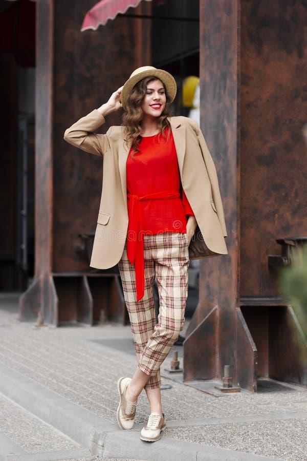 Het modieuze jonge meisje in in vrijetijdskleding gekleed in een jasje en een hoed stelt in de straat op een de zomerdag stock afbeeldingen