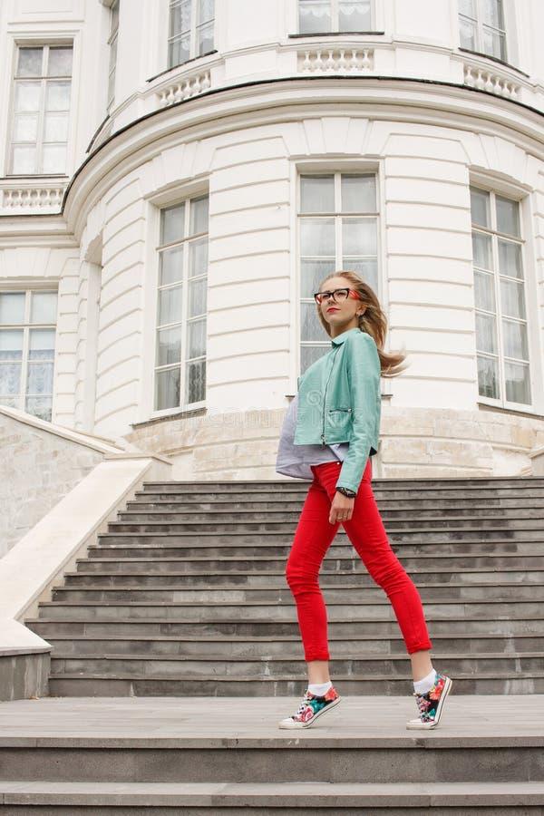 Het modieuze jonge slanke blondemeisje stellen op de treden De modieuze vrouw ` s kijkt royalty-vrije stock afbeelding
