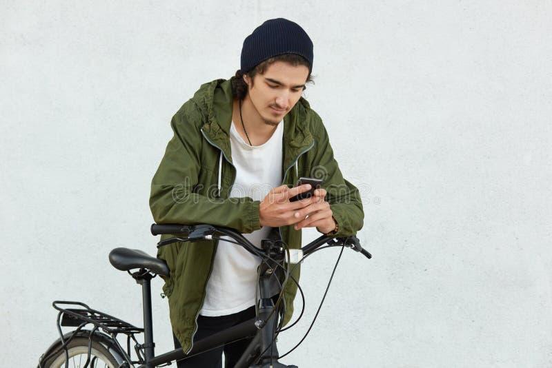 Het modieuze kereltje in zwarte hoed en het jasje met kap, hebt actieve levensstijl, behandelt lange afstanden met zijn sportfiet stock foto's