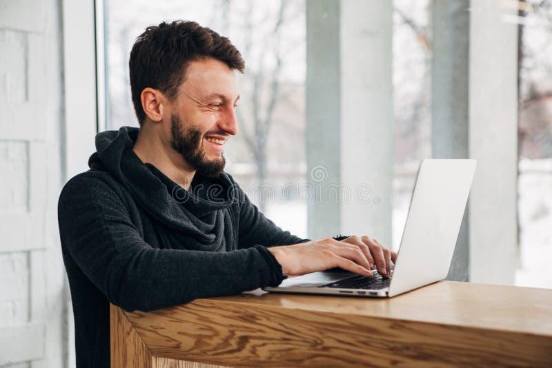 Het modieuze mannelijke freelancer werken aan nieuw startproject die Internet-onderzoekers maken die gegevens analyseren die lapt royalty-vrije stock afbeelding
