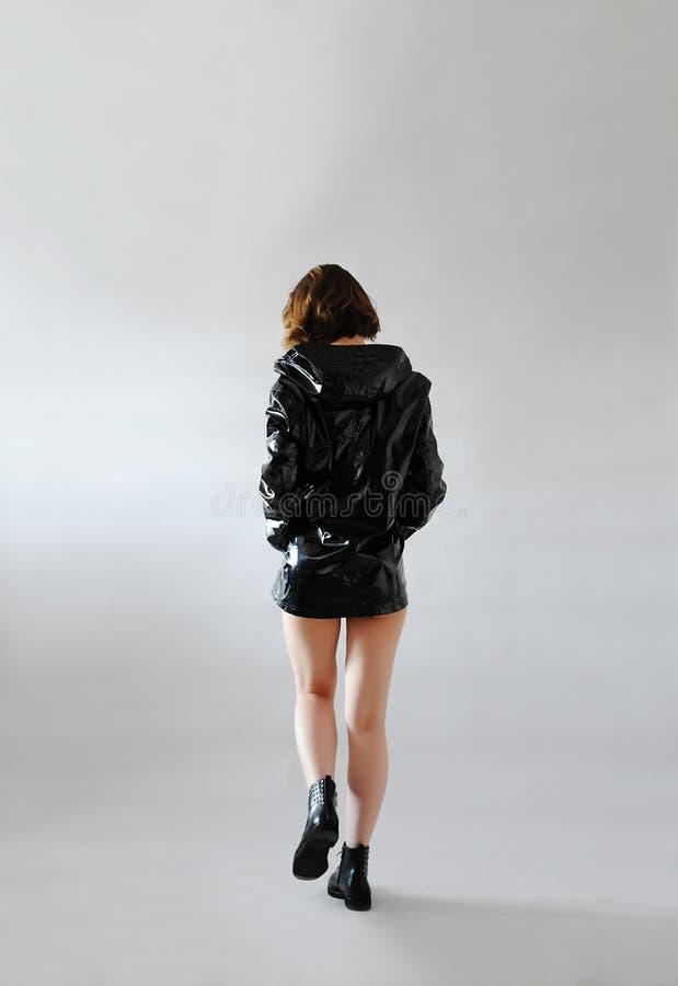 Het modieuze meisje in de zwarte gelakte regenjas van het regenjasje met kap gaat achtermening weg Lichte achtergrond In uitrusti stock foto