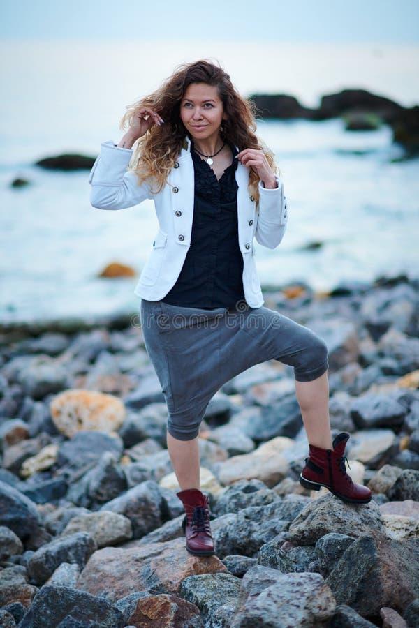 Het modieuze meisje kleedde zich in wit jasje en brede broeken die dichtbij overzees in de avond stellen stock afbeelding