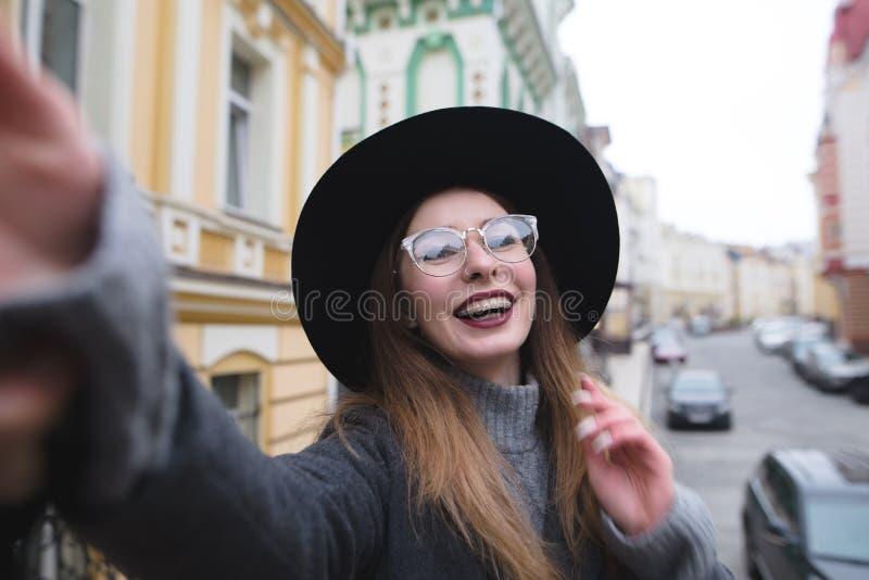 Het modieuze meisje met steunen neemt selfie krasvoho tegen de achtergrond van het stedelijke landschap stock afbeeldingen