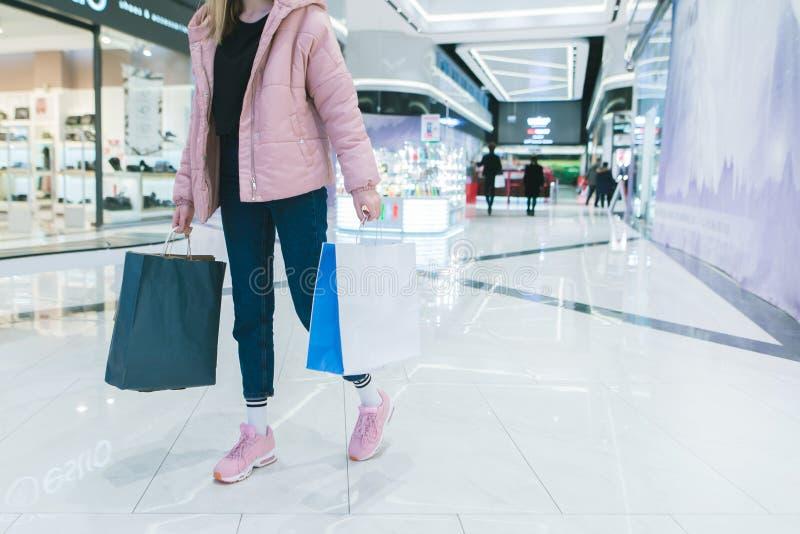 Het modieuze meisje met het winkelen in haar handen loopt door een modern, mooi winkelcomplex Het meisje winkelt royalty-vrije stock foto