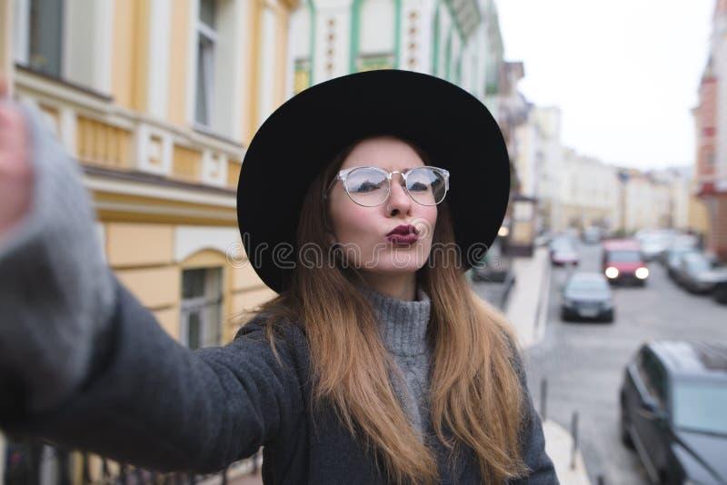 Het modieuze meisje neemt selfie straat terwijl het lopen rond de mooie stad stock foto