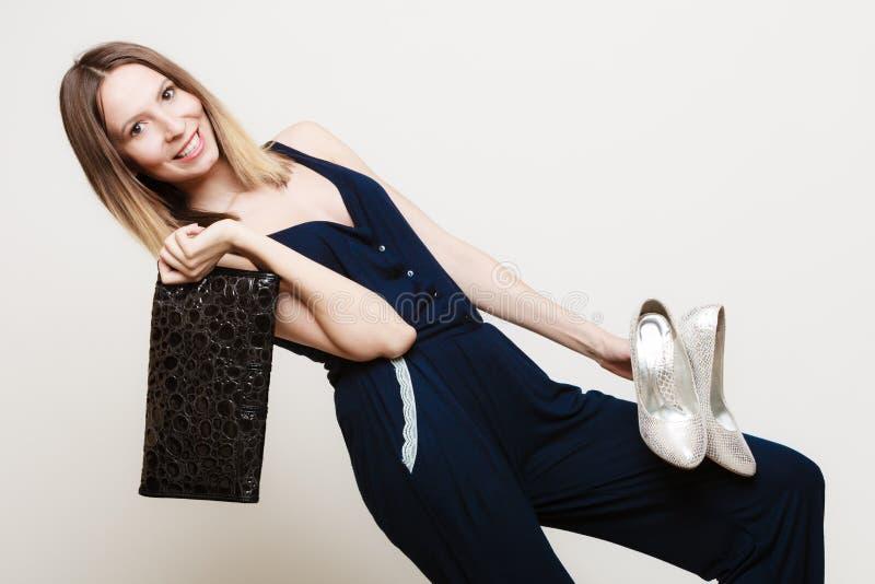 Het modieuze meisje van de vrouwenmanier houdt handtas en schoenen royalty-vrije stock afbeelding