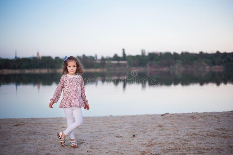 Het modieuze meisje in witte broeken dichtbij het meer De kindkosten blootvoets op zand royalty-vrije stock foto's