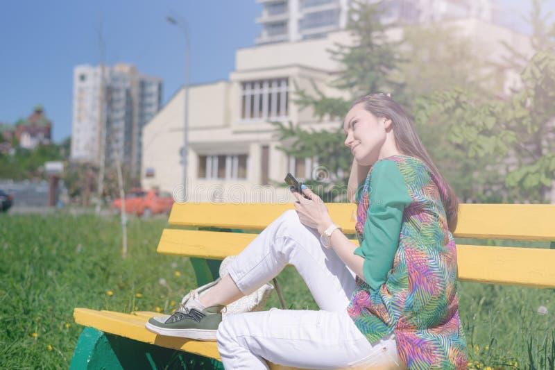 Het modieuze meisje in witte jeans en groene blouse zit op een gele bank en geniet van smartphone, online mededeling, sociale net royalty-vrije stock fotografie