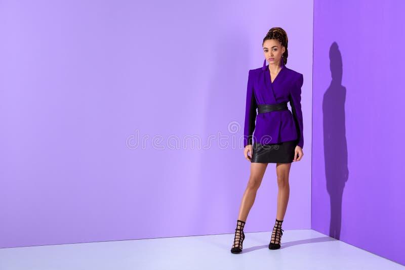 het modieuze mooie mulat model stellen in purper jasje ultra stock foto's