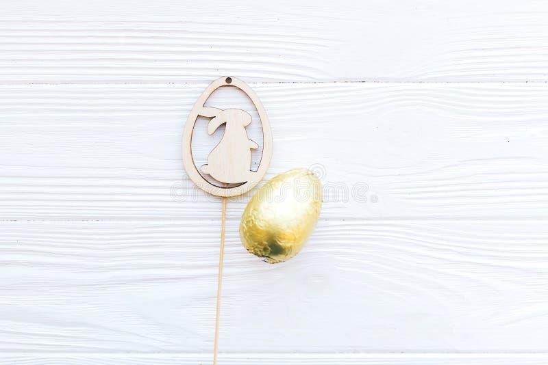 Het modieuze Pasen-chocoladeei in gouden folie en de eenvoudige houten konijntjesdecoratie op witte houten vlakke achtergrond, le stock foto