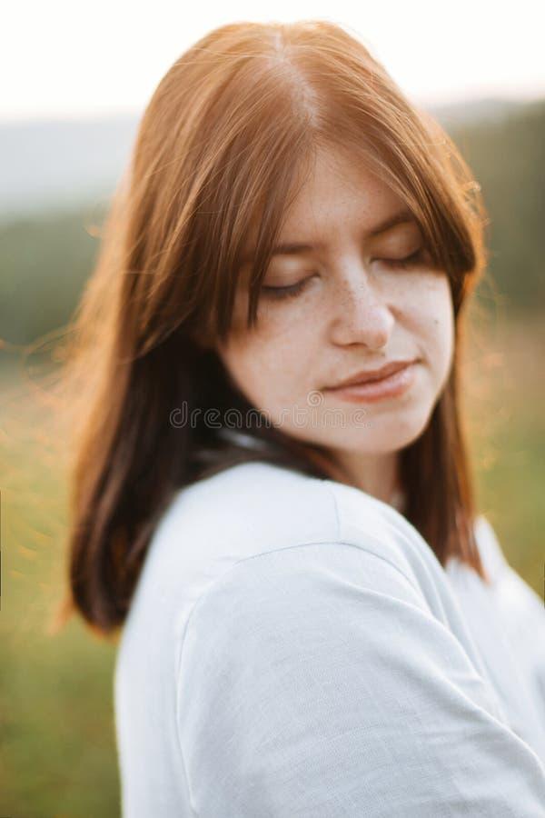 Het modieuze portret van het bohomeisje in zonnige weide bij atmosferische zonsondergang Kalme hipstervrouw in linnen het rustiek royalty-vrije stock afbeeldingen