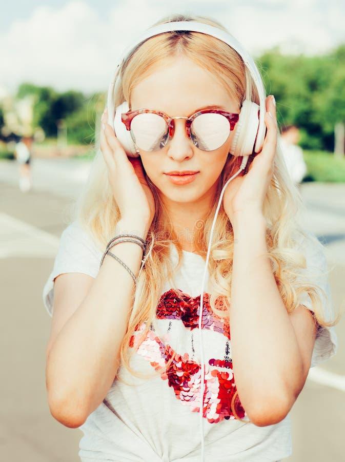 Het modieuze portret van de de zomermanier van het jonge vrij sexy blondemeisje stellen in zonnebril, T-shirt, en het luisteren a stock foto's