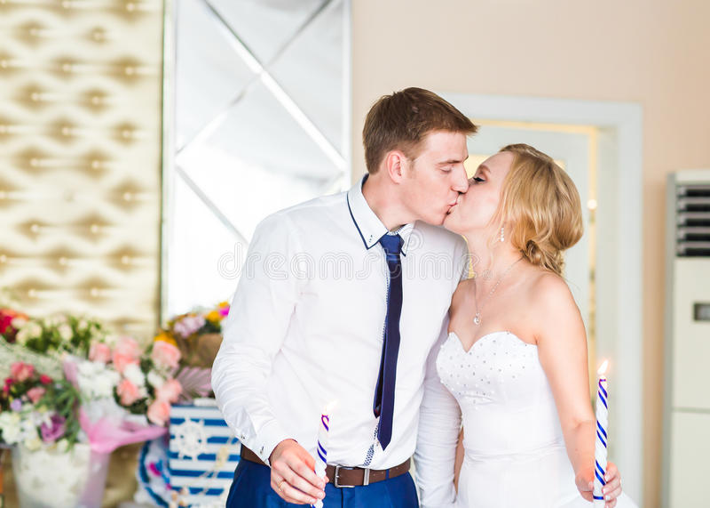 Het modieuze schitterende gelukkige bruid en bruidegom kussen bij huwelijksontvangst, emotioneel vrolijk ogenblik royalty-vrije stock foto's