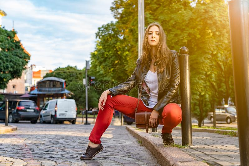 Het modieuze sexy meisjesmodel stelt zitting op de weg op de straat royalty-vrije stock foto