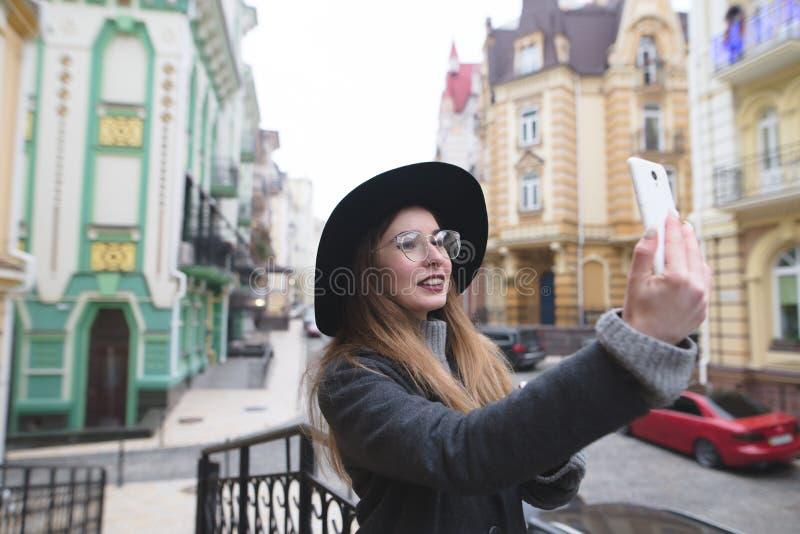 Het modieuze toeristenmeisje neemt selfie op de achtergrond van een mooie oude stad stock afbeeldingen