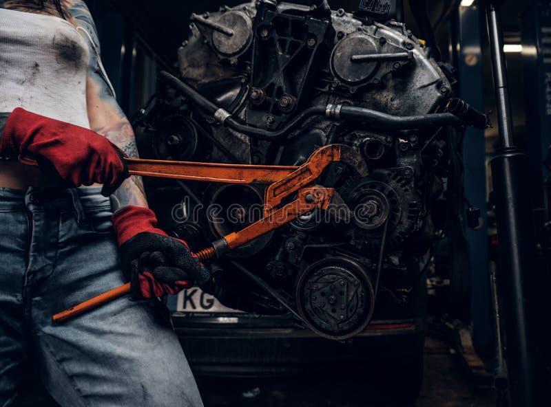 Het modieuze vrouwelijke model met tattoed lichaam herstelt een motor van een auto die op een hydraulisch hijstoestel in de works royalty-vrije stock afbeelding