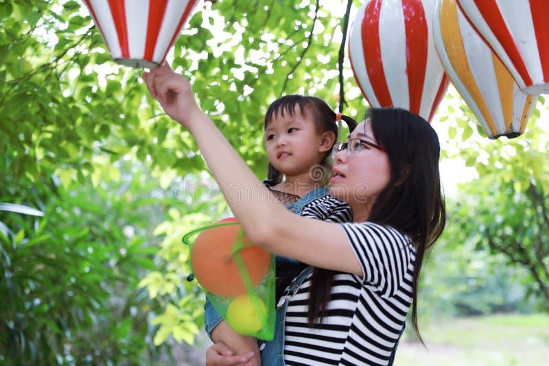Het moedermamma omhelst omhelzing haar lach van de dochterglimlach pret heeft van vrije tijd in spel van het kindkinderjaren van  stock foto