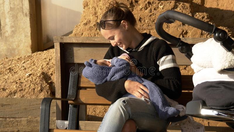 Het moedervoer haar mooie baby buiten het zitten bij banch bij de stad parkeert royalty-vrije stock afbeelding