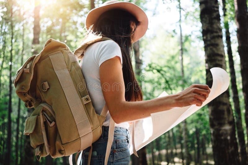 Het moedige hipstermeisje reizen alleen en het kijken rond in bos bij in openlucht het dragen van treveler rugzak en greepplaats  stock fotografie