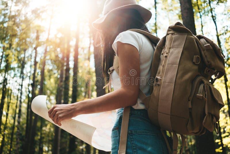 Het moedige hipstermeisje reizen alleen en het kijken rond in bos bij in openlucht het dragen van treveler rugzak en greepplaats  stock foto's
