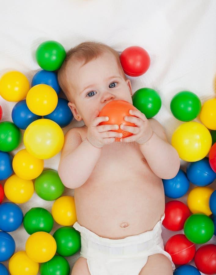 Het mollige babymeisje spelen met kleurrijke ballen royalty-vrije stock foto's