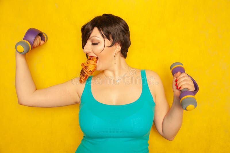 Het mollige blije emotionele meisje met kort haar in een blauwe t-shirt probeert om sporten met domoren te spelen om gezond te zi royalty-vrije stock fotografie