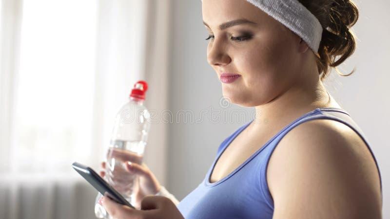 Het mollige dame scrollen op smartphone, die nieuwe uiteinden zoeken om extra gewicht te verliezen royalty-vrije stock foto