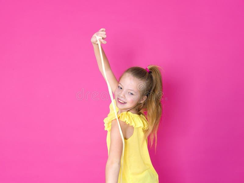 Het mooie 10 éénjarigenmeisje speelt met geel slijm voor roze achtergrond en is gelukkig royalty-vrije stock fotografie