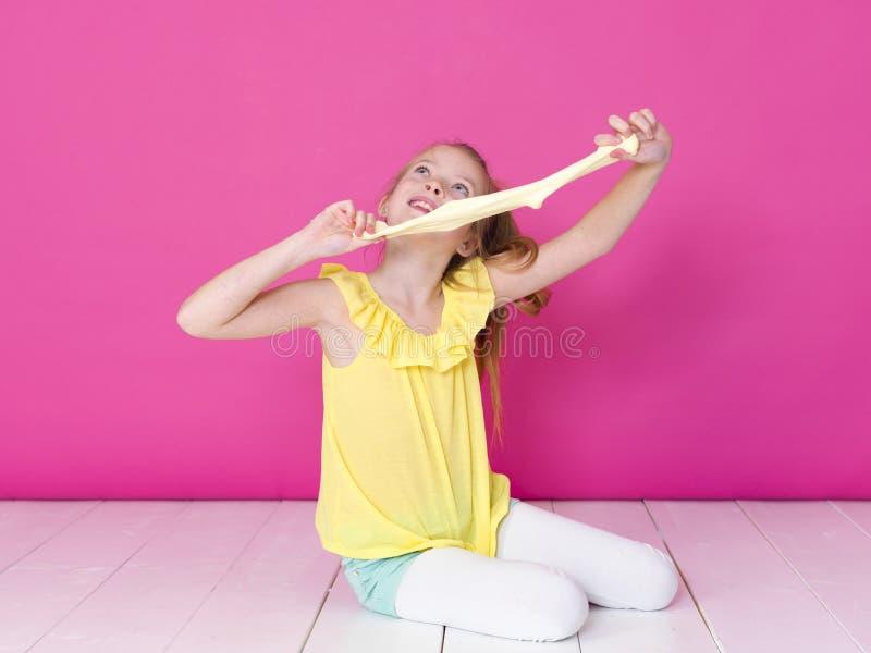 Het mooie 10 éénjarigenmeisje speelt met geel slijm voor roze achtergrond en is gelukkig royalty-vrije stock foto's