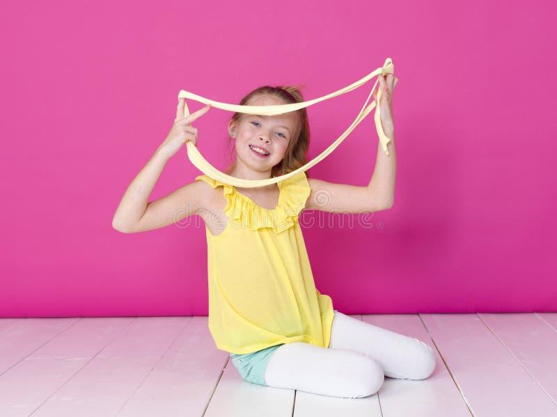 Het mooie 10 éénjarigenmeisje speelt met geel slijm voor roze achtergrond en is gelukkig royalty-vrije stock afbeeldingen