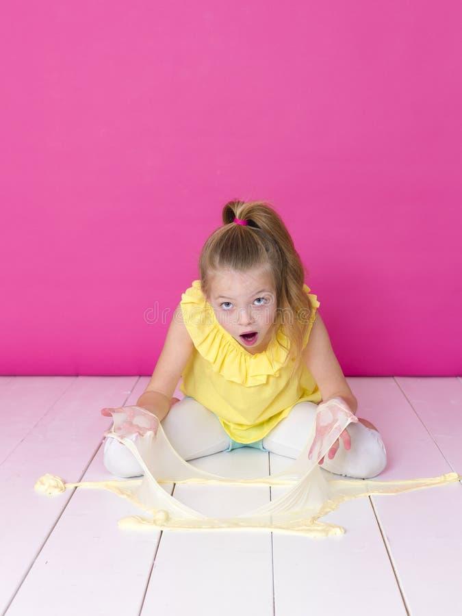 Het mooie 10 éénjarigenmeisje speelt met geel slijm voor roze achtergrond en is gelukkig stock foto's