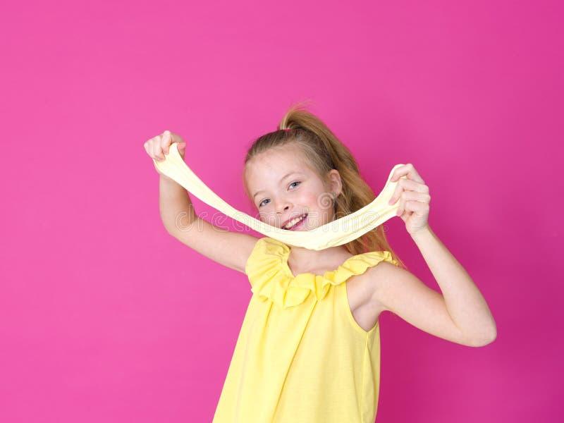 Het mooie 10 éénjarigenmeisje speelt met geel slijm voor roze achtergrond en is gelukkig royalty-vrije stock foto