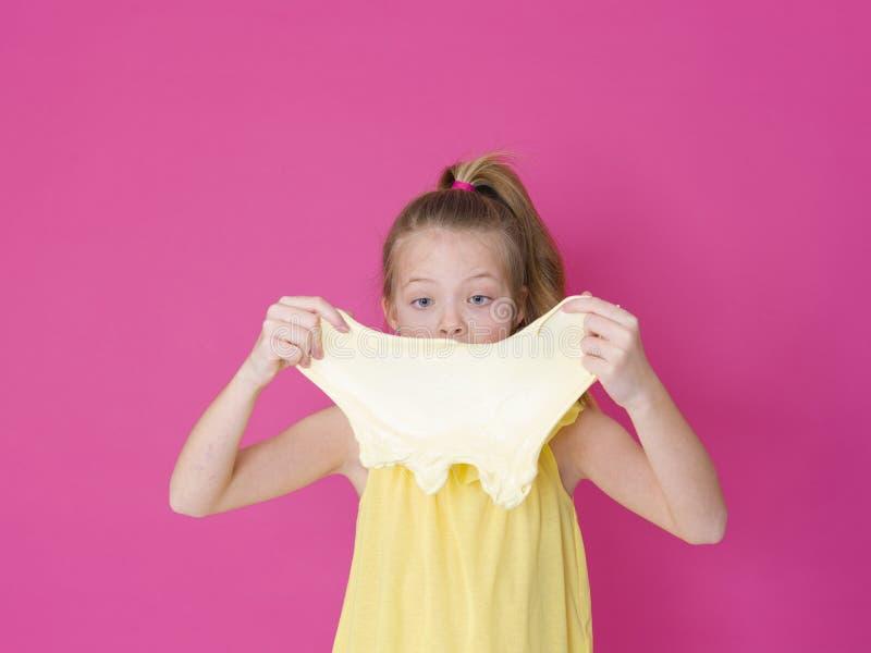 Het mooie 10 éénjarigenmeisje speelt met geel slijm voor roze achtergrond en is gelukkig stock fotografie