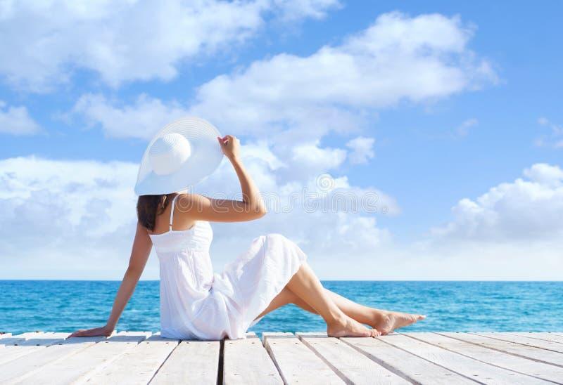 Het mooie, aantrekkelijke model stellen in witte kleding op een houten pijler Overzeese en Hemelachtergrond Vakantie, die reizen  royalty-vrije stock afbeelding