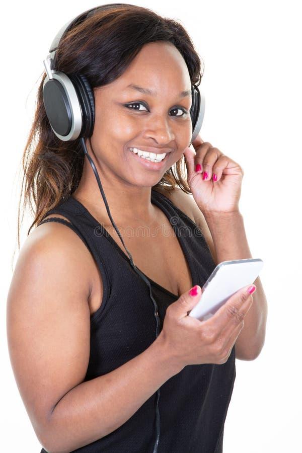 Het mooie Afrikaanse Amerikaanse jonge vrouw blije luisteren aan muziek op mobiele telefoon stock foto's